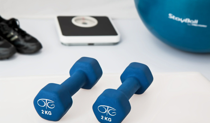 Două gantere de două kilograme de culare albastra, un cântar și o minge de fitness