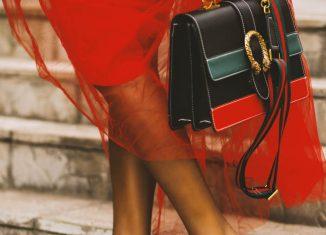 femeie care tine in mana o geanta din piele
