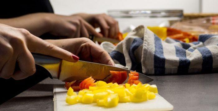 femeie care taie legumele cu cutiul