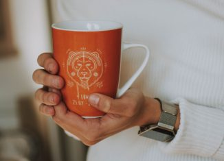 femeie care tine in mana o cana cu cafea inscriptionata cu un semn zodiacal