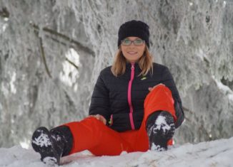 femeie imbracata in costum de ski care sta in zapada