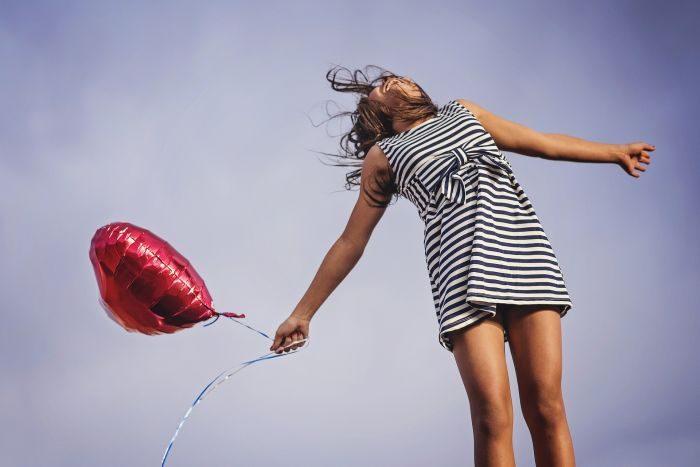 femeie fericita care are un balon in mana