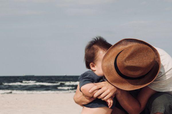 tata care isi imbratiseaza copilul mc pe plaja
