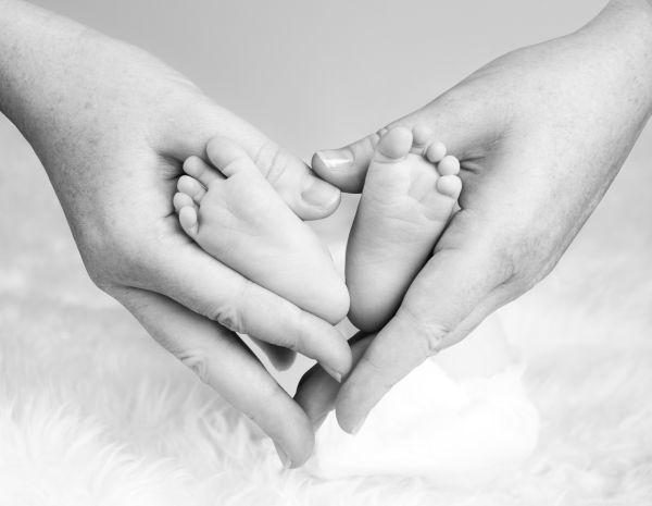 mama care tine in palme piciorusele bebelusului