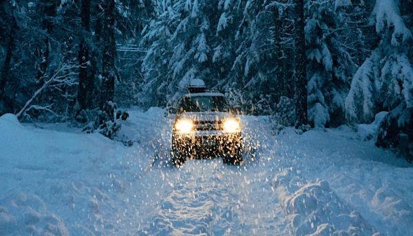 masina cu farurile aprinse care merge oprin zapada pe un drum de munte