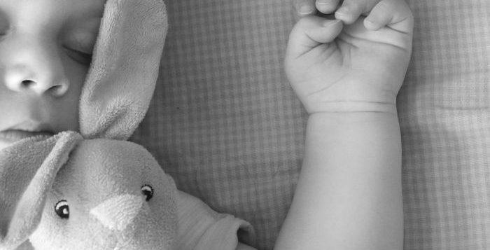 copil care doarme cu jucaria preferata in patut