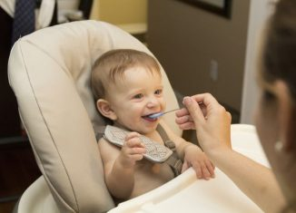 copil care mananca din lingurita