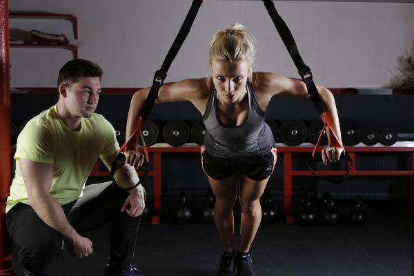 femeie la sala de fitness alaturti de instructor