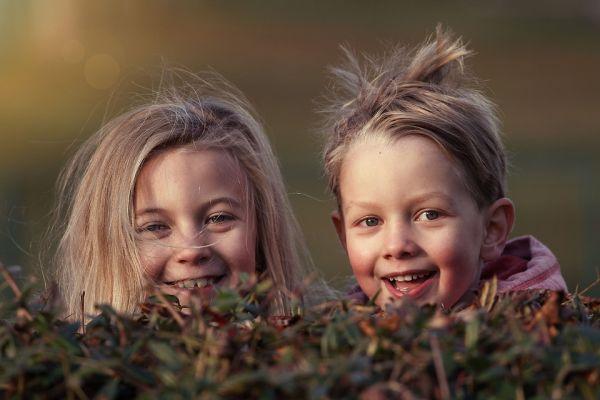 copii fericiti care rad ascunsi in iarba