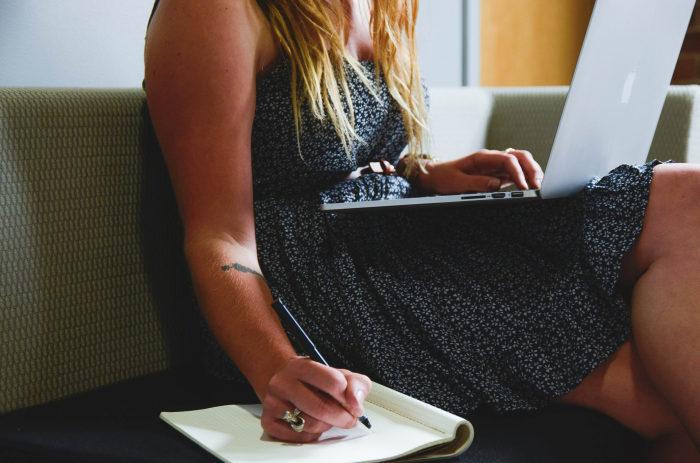 femeie care sta pe canapea cu un laptop in brate si scrie intr-o agenda