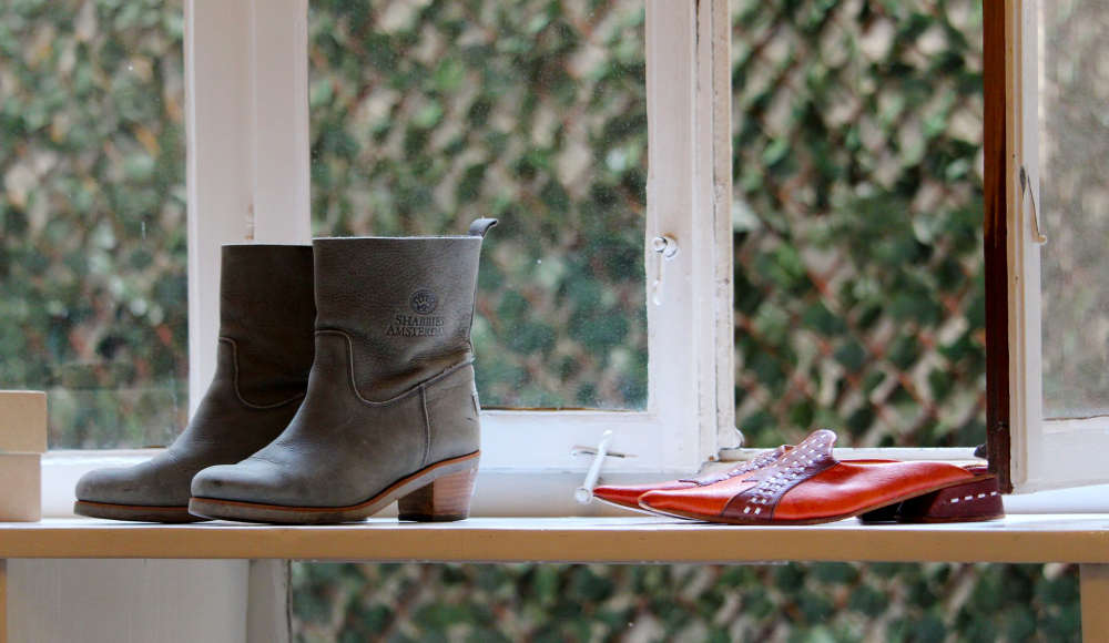 cizme de iarna si pantofi pe un raft in fata unui geam in magazin