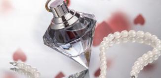 sticlacu parfum langa un sirag de perle
