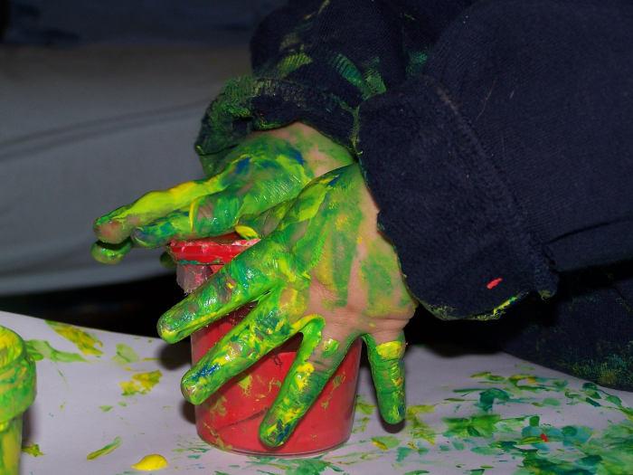 Copil mic care picteaza cu degetele si este murdar de vopsea galbena pe maini