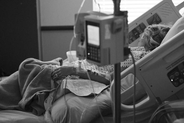 Femeie pacient pe patul de spital in sectia de terapie intensiva si conectata la aparate