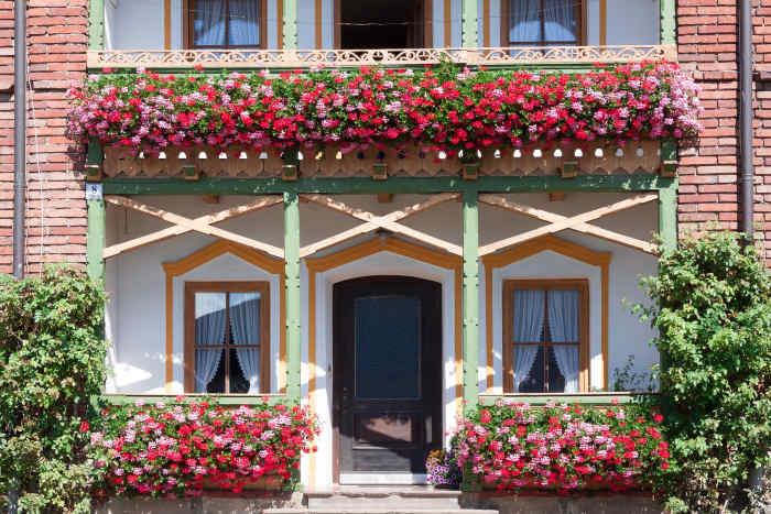 Balcoane mari într-o vilă, decorate cu ghivece cu flori roșii