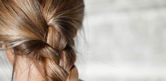 Femeie cu părul împletit care folosește tratament pentru păr deteriorat