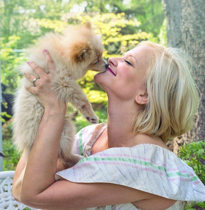 Femeie care pupă un câine în bot